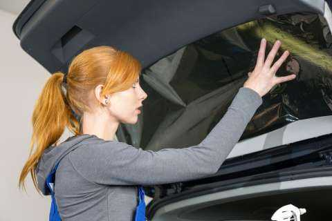 Car wrappers tinting a vehicle window with a tinted foil or film using heat gun and squeegee